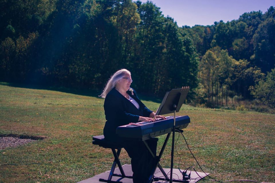 "Deborah ""Ingy"" Ingersoll playing piano outside"
